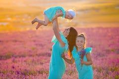 Den härliga familjen av gulliga flickor tycker om på liv med ängen för solnedgången för flickamakt av lavendel Gå mamman och dött fotografering för bildbyråer