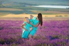 Den härliga familjen av gulliga flickor tycker om på liv med ängen för solnedgången för flickamakt av lavendel Gå mamman och dött royaltyfri bild