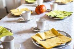Den härliga festliga matställetabellen som den färgrika gula nedgången helloween pumpagarneringkaffe, rånar tefatplattor och sked Royaltyfri Foto