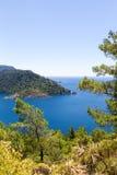 Den härliga fjärden i det Aegean havet med blått vatten och sörjer träd i bergen Royaltyfria Bilder