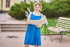 Den härliga flicka-konstnären på gatan i en blå klänning drar en skissa av bilden Fotografering för Bildbyråer
