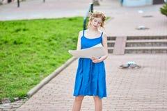 Den härliga flicka-konstnären på gatan i en blå klänning drar en skissa av bilden Arkivfoton