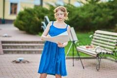 Den härliga flicka-konstnären på gatan i en blå klänning drar en skissa av bilden Royaltyfria Bilder