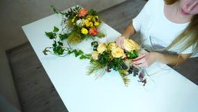Den härliga flickablomsterhandlaren skapar blommaordningen som i regeringsställning sitter på tabellen i dag stock video