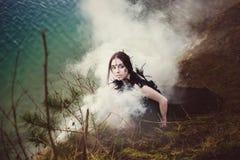 Den härliga flickahäxan trollar i träna Arkivfoto