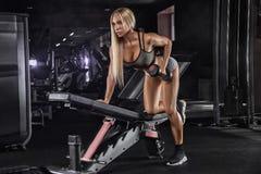 Den härliga flickakroppsbyggaren, utför övning med hantlar, i mörk idrottshall royaltyfria foton