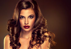 Den härliga flickamodellen med lång brunt krullade hår arkivfoto