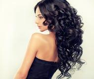 Den härliga flickamodellen med lång svart krullade hår royaltyfri fotografi