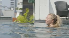 Den härliga flickan är avslappnande i en oändlighetspöl stock video