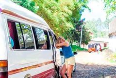 Den härliga flickan är den stående benägenheten på ett minibussfönster Arkivbilder