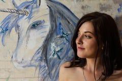 Den härliga flickan är en konstnär med en målad enhörning Arkivfoton