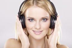 Den härliga flickan är lyssnar till musiken royaltyfri bild