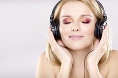 Den härliga flickan är lyssnar till musiken Arkivbild