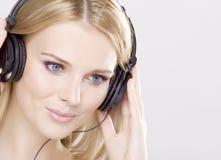 Den härliga flickan är lyssnar till musiken royaltyfri foto