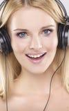 Den härliga flickan är lyssnar till musiken royaltyfri fotografi