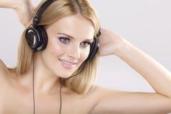 Den härliga flickan är lyssnar till musiken royaltyfria bilder