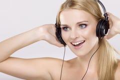 Den härliga flickan är lyssnar till musiken royaltyfria foton