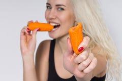 Den härliga flickan äter grönsaker och leenden Royaltyfri Bild