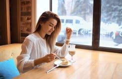Den härliga flickan äter kakan Arkivfoton