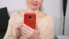 Den härliga flickan använder en cell- smartphone, medan sitta i vardagsrummet i aftonen lyckligt le kvinnabarn arkivfilmer