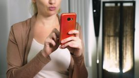 Den härliga flickan använder en cell- smartphone, medan sitta i vardagsrummet i aftonen lyckligt le kvinnabarn lager videofilmer