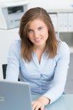 Den härliga flickan arbetar på datoren Arkivfoto
