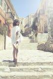 Den härliga flickan badade i solsken som går i den forntida staden Symi Arkivbilder