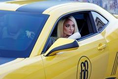 Den härliga flickan, bantar modellen som är blond, bilen, vägen som är utomhus- Arkivfoto