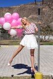 Den härliga flickan, blondinen står på en ljus kula och rymmer många ballonger royaltyfri bild