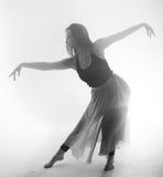 Den härliga flickan dansar elegantly i rök och dimma Fotografering för Bildbyråer