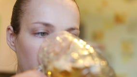 Den härliga flickan dricker ett stort exponeringsglas av öl stock video