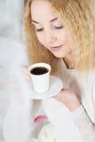 Flickan dricker kaffe i en morgon Arkivfoton