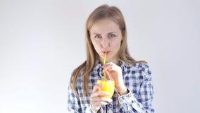 Den härliga flickan dricker nytt sammanpressad orange fruktsaft till och med ett sugrör lager videofilmer