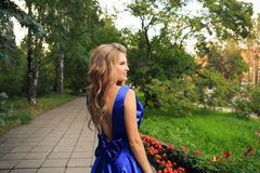 Den härliga flickan går i en blå klänning fotografering för bildbyråer