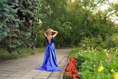 Den härliga flickan går i en blå klänning royaltyfri foto