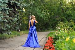 Den härliga flickan går i en blå klänning royaltyfria bilder