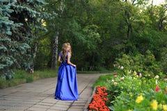 Den härliga flickan går i en blå klänning arkivfoton