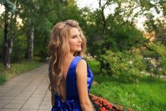 Den härliga flickan går i en blå klänning royaltyfri fotografi