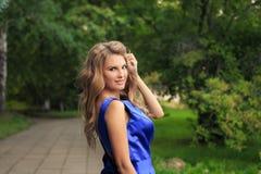 Den härliga flickan går i en blå klänning arkivbilder