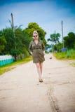 Den härliga flickan går på en lantlig väg. Royaltyfri Foto
