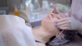 Den härliga flickan gör ansikts- behandling på kosmetologen lager videofilmer