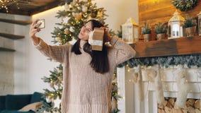 Den härliga flickan gör direktanslutet den videopd appellen med smartphonen på anseende för juldag nära spisen och gran-träd arkivfilmer