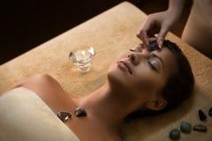 Den härliga flickan har massage med chakra-stenar royaltyfri foto