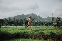 Den härliga flickan hoppar, de oerhörda risfälten, en vulkan i bakgrunden och bergen kall bakgrund Lyckligt royaltyfri foto