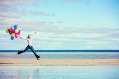 Den härliga flickan hoppar på stranden, medan rymma Fotografering för Bildbyråer