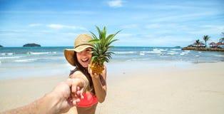 Den härliga flickan i baddräkt och ananas går på stranden som rymmer handen av grabben Royaltyfria Bilder