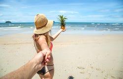 Den härliga flickan i baddräkt och ananas går på strandhållen Arkivfoto