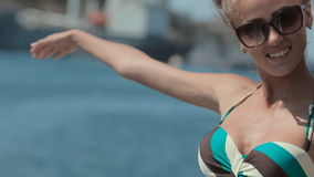 Den härliga flickan i bikini kör på yachten förbi stock video