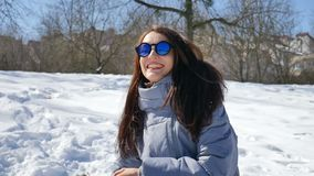 Den härliga flickan i blå spegelförsedd solglasögon och rakt kasta för mörkt hår kastar snöboll att spela med något utomhus in arkivfilmer
