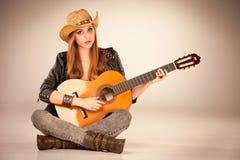 Den härliga flickan i cowboys hatt och akustiska gitarr Royaltyfri Bild